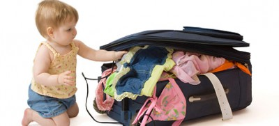 Baby kneeling, packing the suitcase